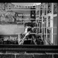 a self-portrait in front of a mirror in black and white