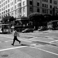 Picture in black & white of a woman crossing the streets at a crossroad in San Francisco.
